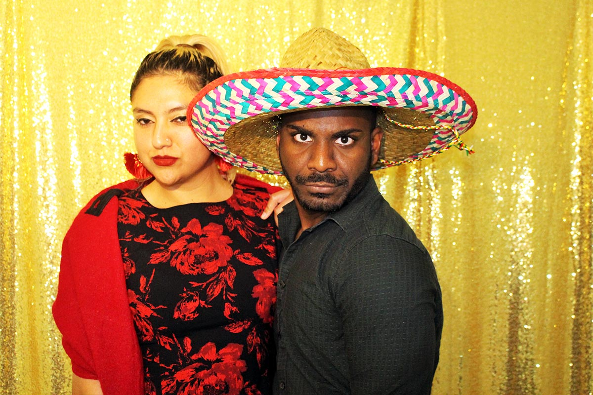 couple posing with a sombrero in our Houston photo booth